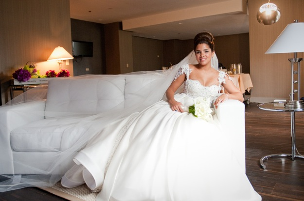 bride in traditional white wedding dress relaxes on couch