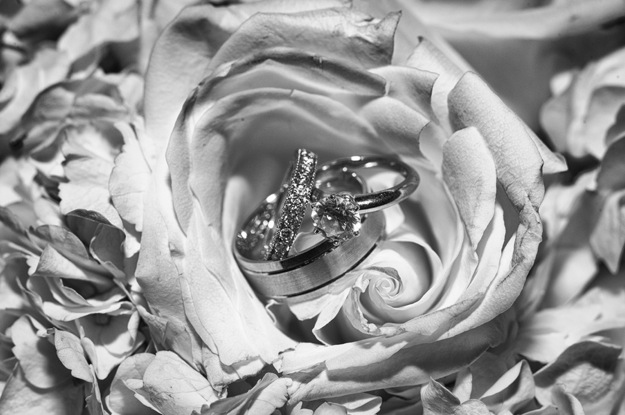 wedding rings rest inside flower