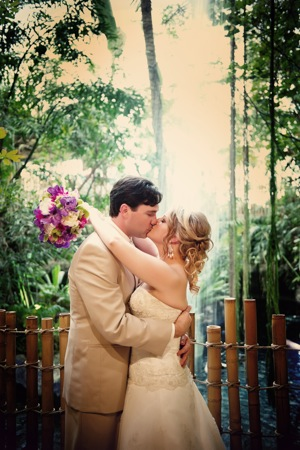 groom and bride in rainforest setting kiss