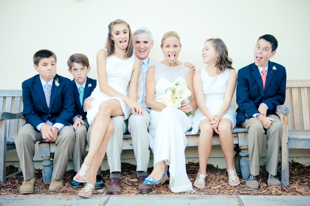 bride and groom and their children pose for silly wedding portrait