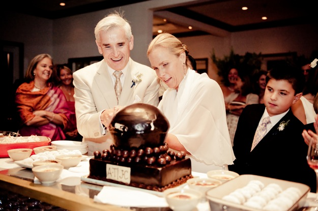 bride and groom cut large round chocolate cake