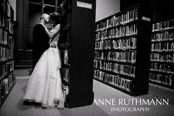 bride and groom kiss in bookshelves at library