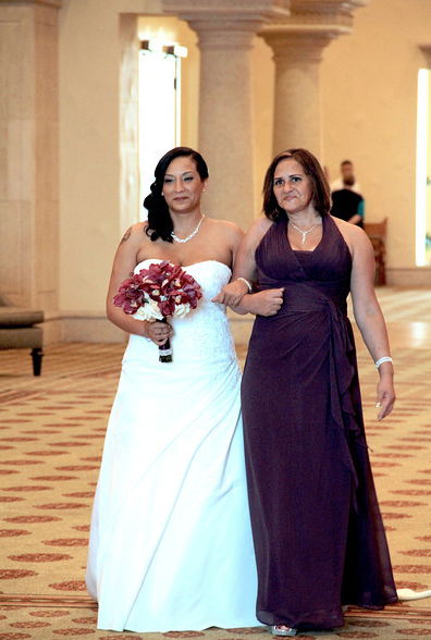 mother of the bride and bride walk to aisle