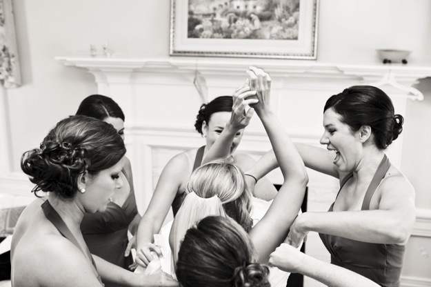 bridesmaids help bride get dressed before wedding