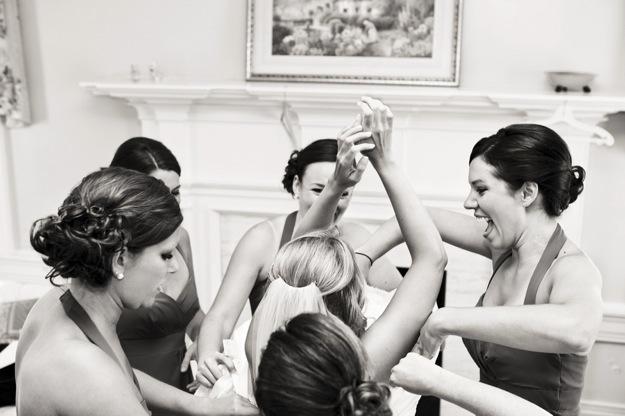 bridesmaids help bride get dressed before wedding