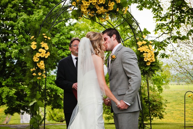 bride and groom kiss at outdoor wedding ceremony