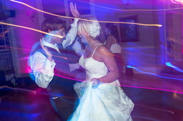 lighting effects surround bride and groom dancing