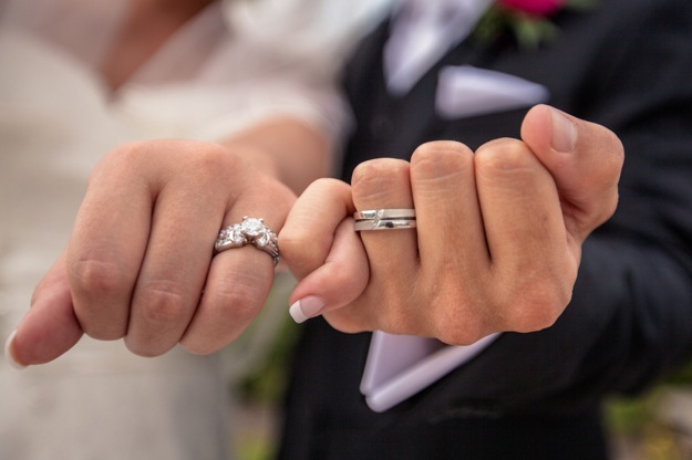 bride and groom link pinkies with silver wedding rings
