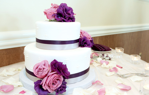 two layer white wedding cake with rose and purple flowers