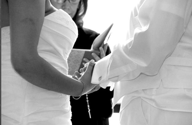 brides hold hands during wedding