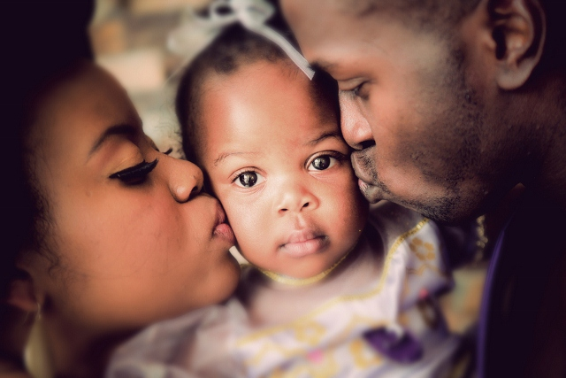 African American Bride and groom kiss daughter