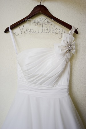 white wedding dress with rose detail on wooden wedding hanger