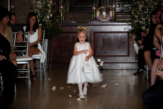 flower girl in short white dress walks down the aisle