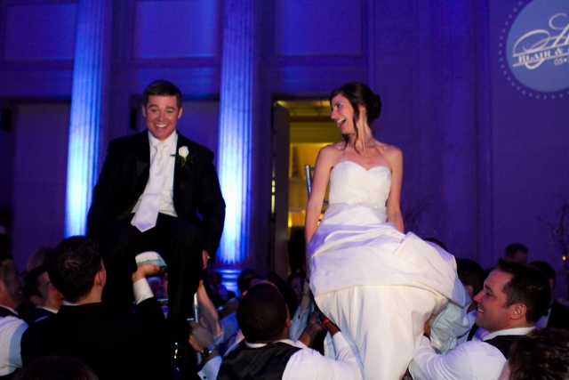 bride and groom on chairs for hora dance