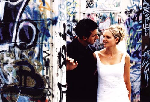 wedding photography of bride and groom against wall with grafitti