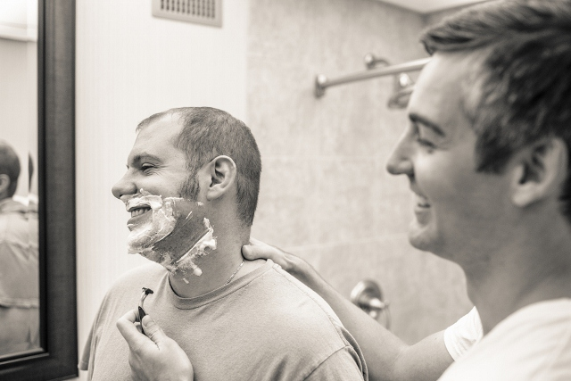 best man shaves groom before wedding