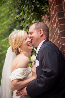 bride and groom laugh while kissing