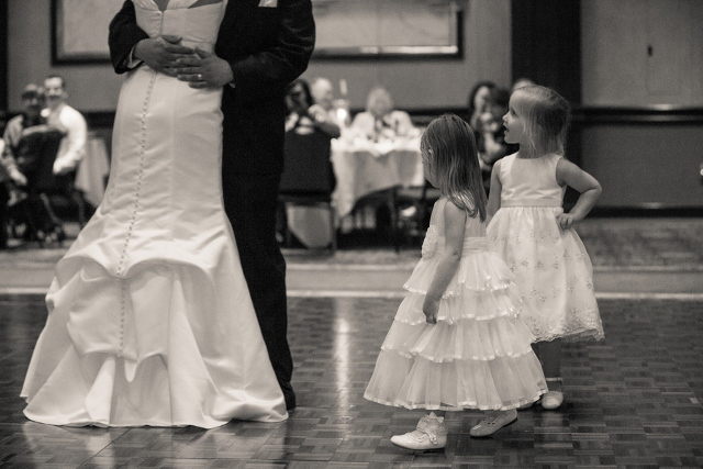 bride and groom dance with flower girls watching
