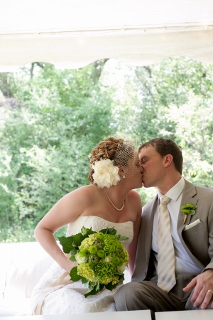 bride and groom kissing with green flowers