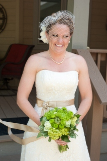 bride in strapless dress with tan sash and green bouquet