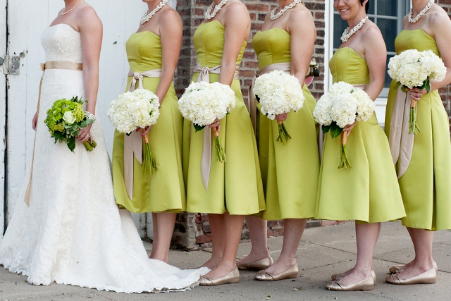 bridesmaids in short green dresses with white bouquets