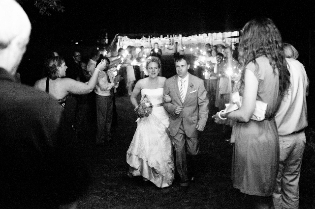 bride and groom leave wedding with sparklers