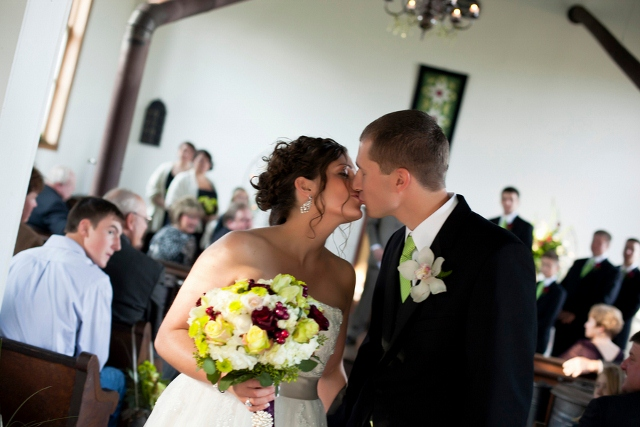 groom and bride kiss in church