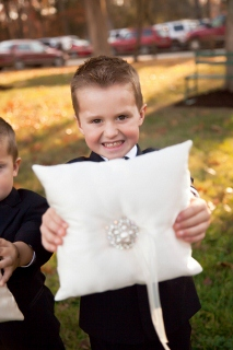 young ring bearer holds pillow