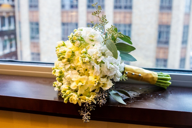 yellow wedding bouquet with ribbon on window sill