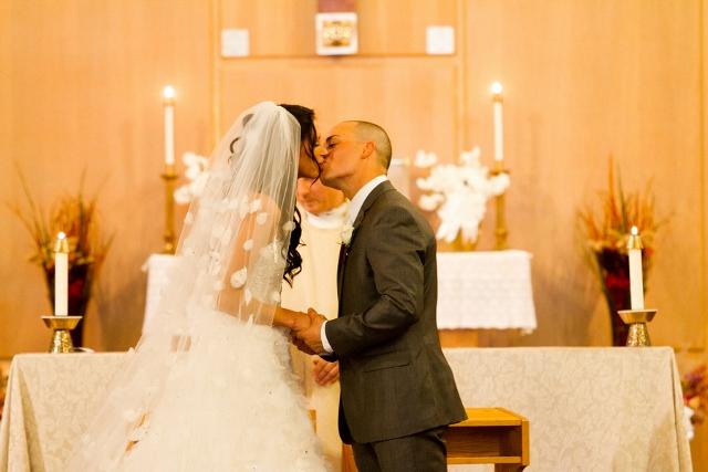 couple kissing at altar
