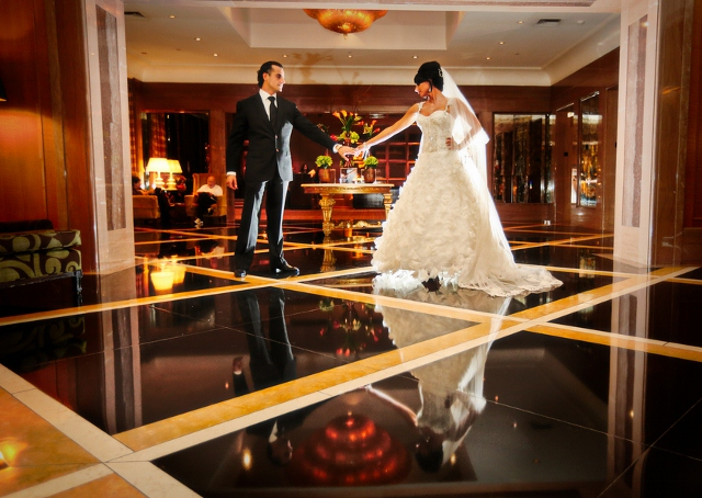 groom and bride pose in ballroom