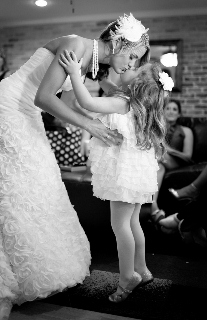 small girl and bride kiss