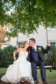 bride and groom kiss on swing