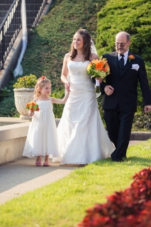 bride and daughter walk down aisle with father of the bride