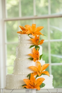 orange flowers on white wedding cake