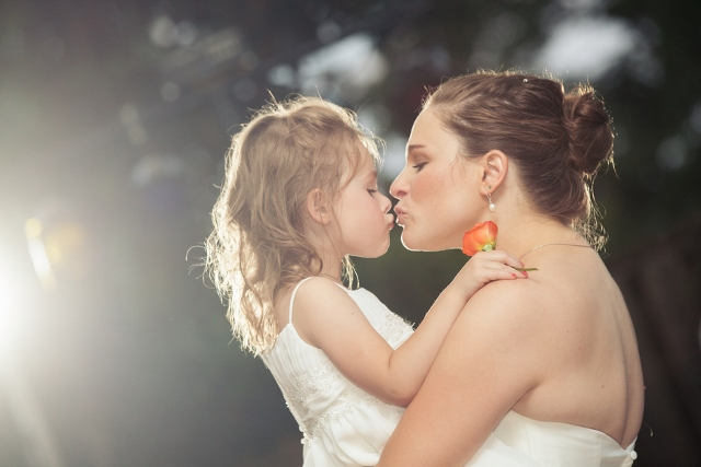 bride and young daughter kiss