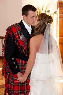 groom in scottish dress kisses bride